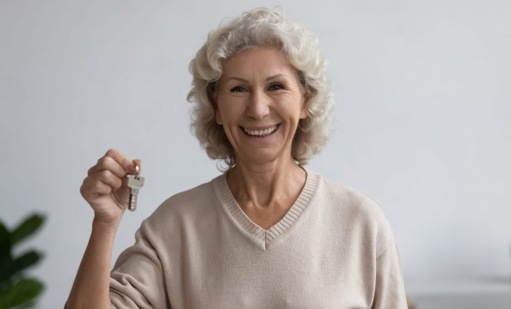 Happy,Old,Woman,Holds,Bunch,Of,Keys,Standing,Indoors,Smile